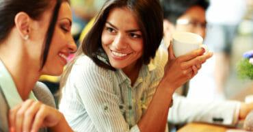 Conversazione in lingua inglese; giovane lavoratrice con colleghi durante una pausa caffè